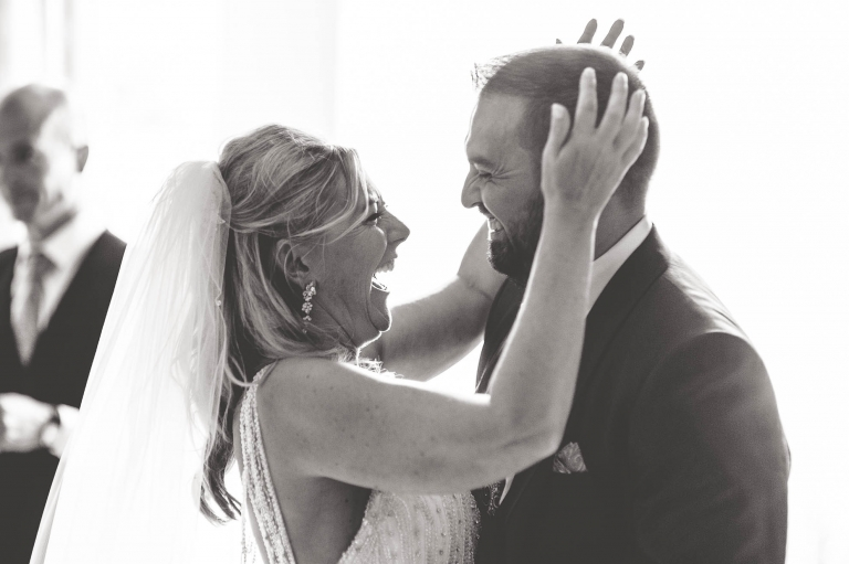 Bride and groom hug and laugh together