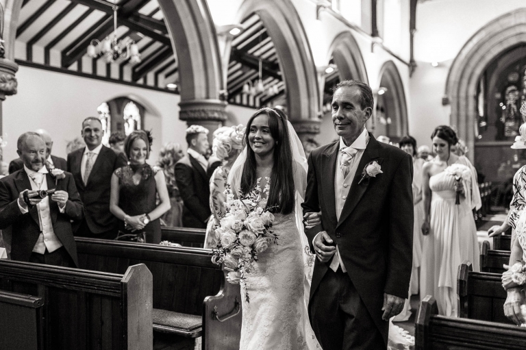 the bride smiles at the groom as she walks up the church aisle with her father