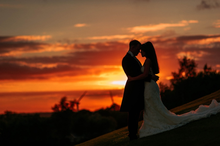 Bride and groom hold each other with a beautiful sunset