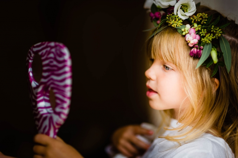 flower girl looks in mirror