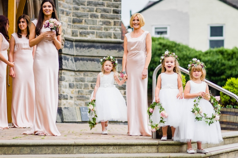 The bridesmaids look on and smile as the bride arrives