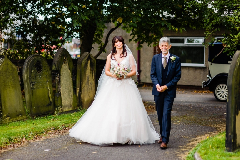 the bride and her father walk to the church