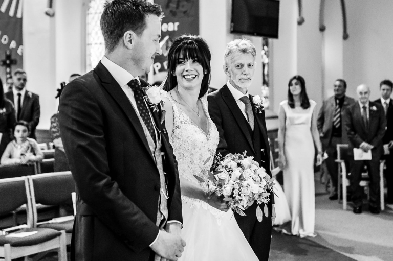 Bride gives the groom a big smile as she arrives at the altar