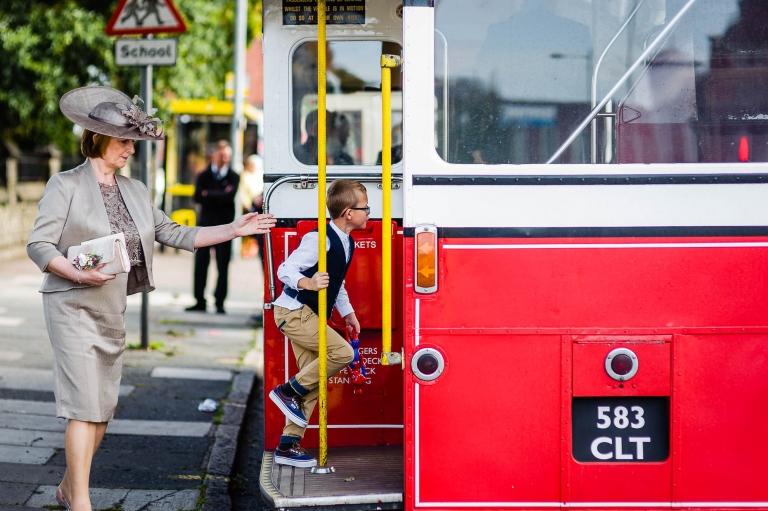 little boy gets on wedding bus