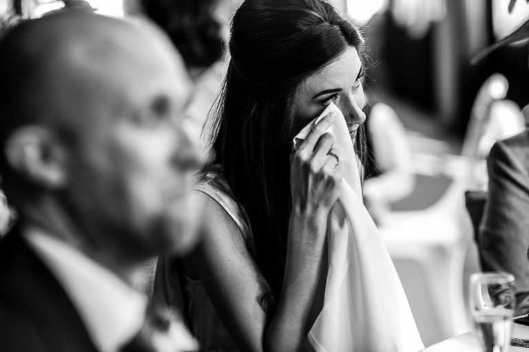 Bridesmaid sheds a tear during groom's speech