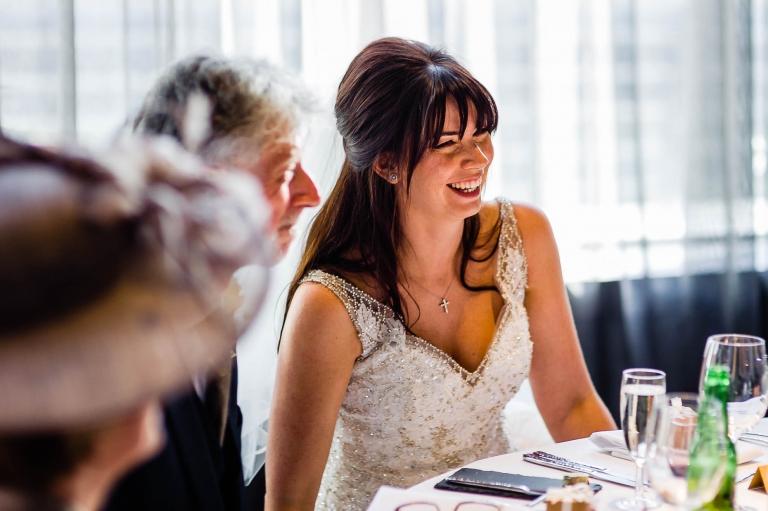 bride laughs during grooms speech