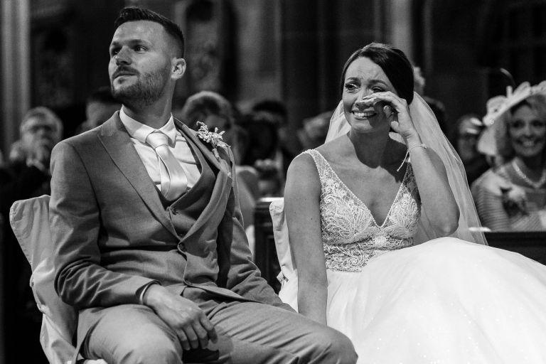 Bride wipes away a tear during wedding